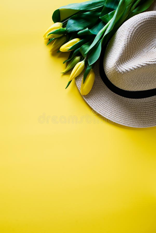 Chapéu e tulipas amarelas sobre o fundo amarelo fotografia de stock