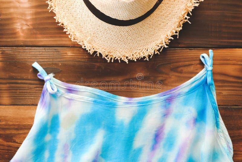 Chapéu essencial dos artigos do curso da vista superior e camiseta de alças azul no fundo de madeira velho vintage do turismo e d foto de stock