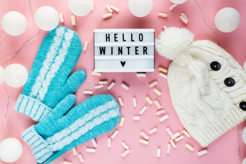 Chapéu morno, acolhedor da roupa do inverno, mitenes, lightbox e decorações do Natal como o quadro no fundo cor-de-rosa pastel foto de stock royalty free