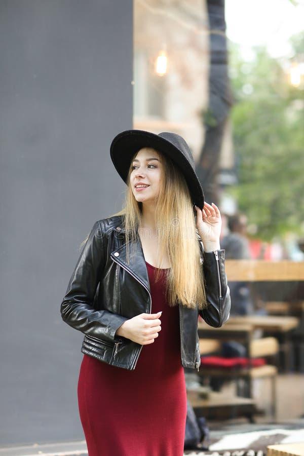 Chapéu negro vestindo da mulher à moda nova e vestido vermelho, casaco de cabedal fotos de stock royalty free