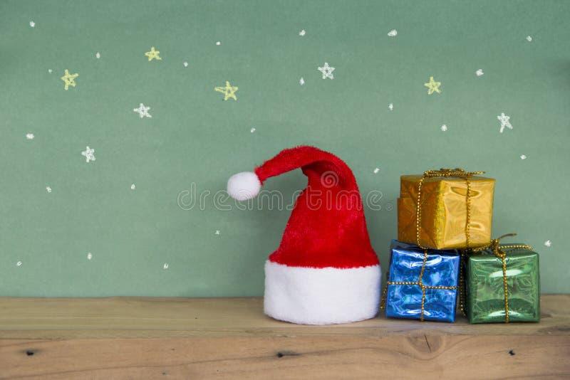 Chapéu vermelho de Santa com a caixa de presente colorida no floorand de madeira fotografia de stock