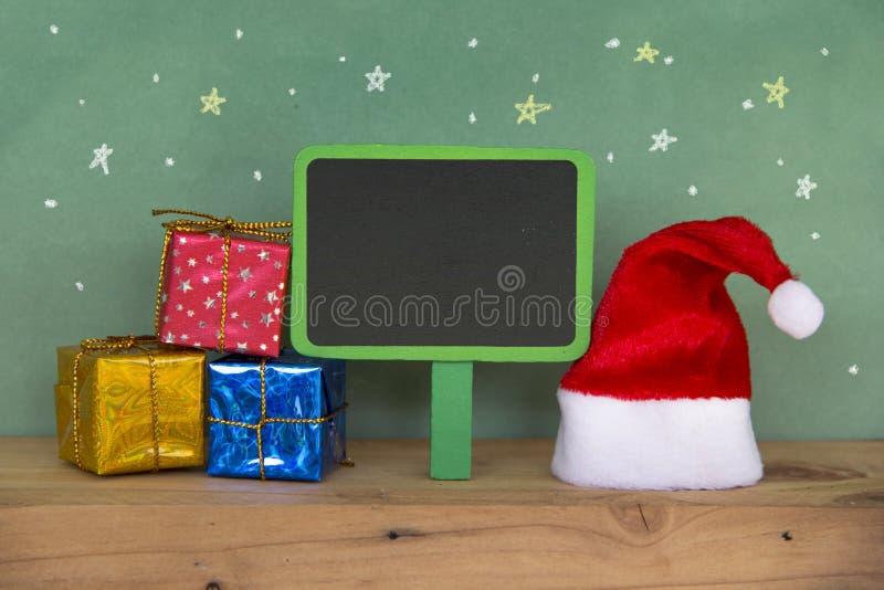 Chapéu vermelho de Santa com a caixa de presente colorida no floorand de madeira imagens de stock