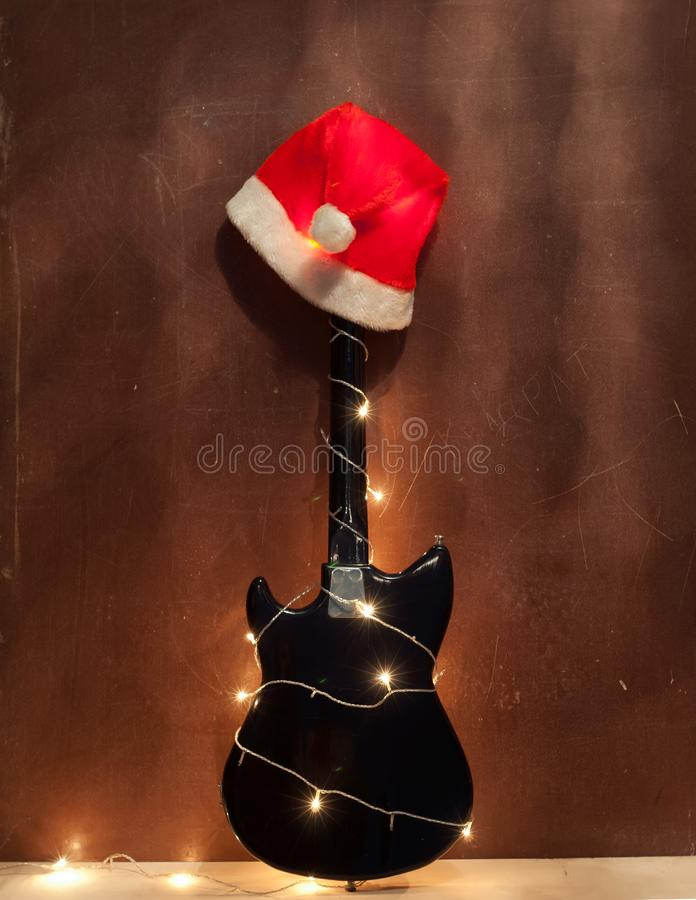 Chapéu vermelho do Natal na guitarra-baixo elétrica preta fotos de stock
