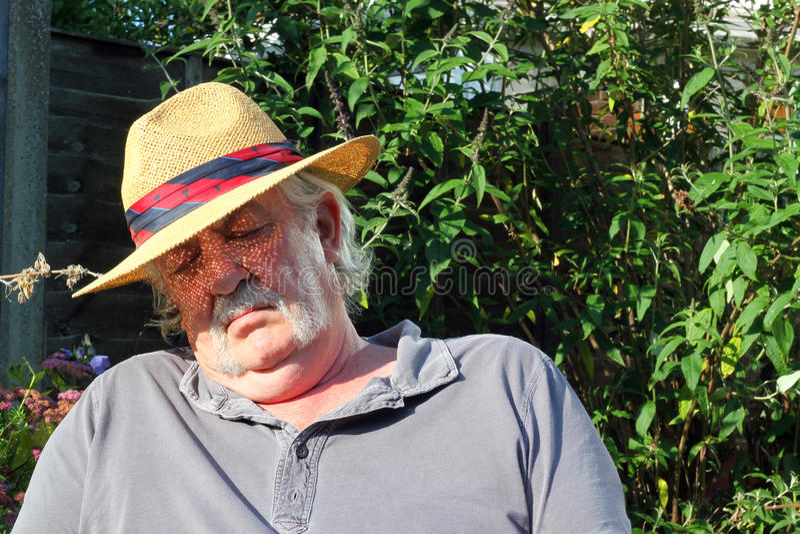 Chapéu vestindo adormecido do homem idoso. fotos de stock