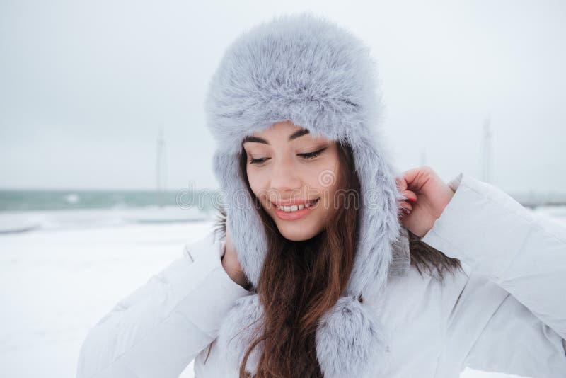 Chapéu vestindo da jovem mulher bonita que anda perto da praia imagens de stock