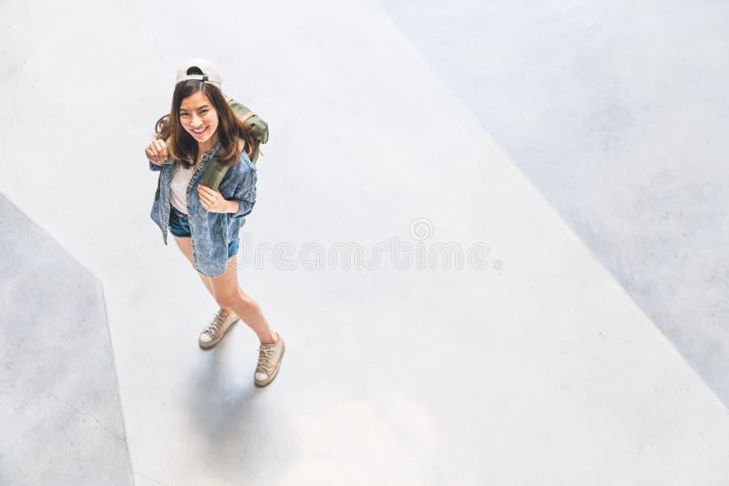 Chapéu vestindo da mulher asiática do viajante da trouxa que olham acima e sorriso, vista superior com espaço da cópia Conceito d imagem de stock royalty free