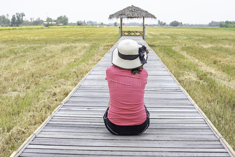 Chapéu vestindo da mulher que senta-se em uma ponte de madeira com uma cabana de bambu nos campos do arroz imagens de stock royalty free