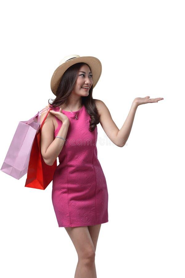 Chapéu vestindo de sorriso da menina asiática que guarda o saco de compras foto de stock royalty free