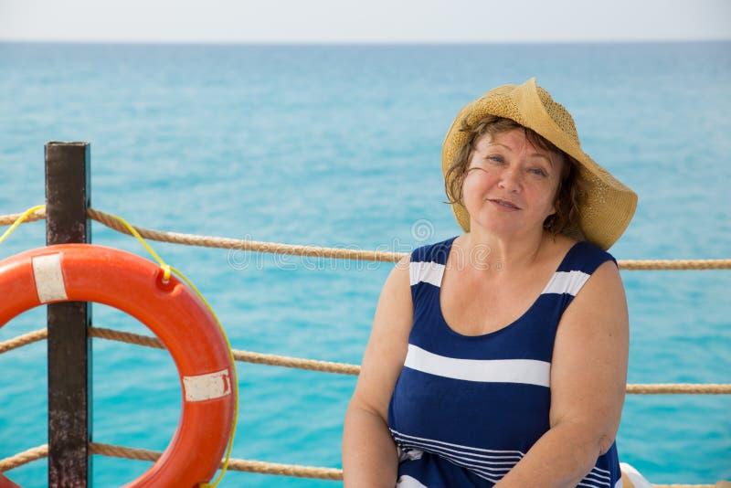 Chapéu vestindo de sorriso da mulher superior na praia com o boia salva-vidas no cais imagens de stock