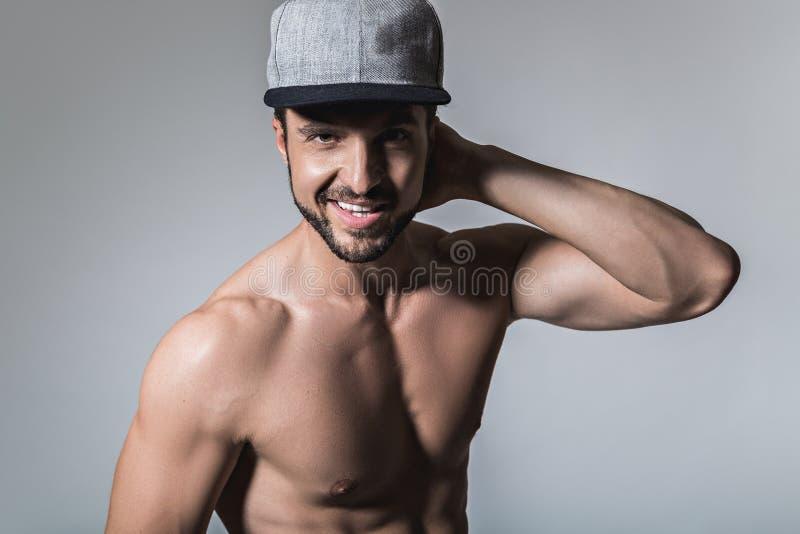 Chapéu vestindo de sorriso do homem descamisado fotografia de stock