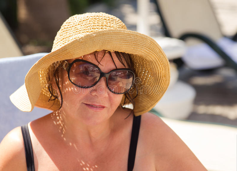 Chapéu vestindo de sorriso e óculos de sol da mulher superior na praia imagem de stock royalty free