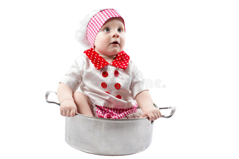 Chapéu vestindo do cozinheiro chefe do menino do cozinheiro do bebê com legumes frescos e frutos foto de stock royalty free