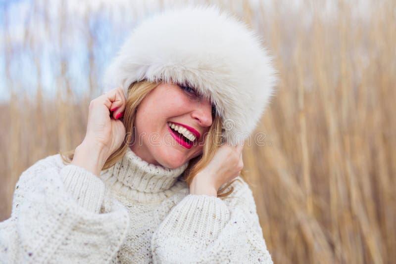 Chapéu vestindo do inverno da mulher feliz fotos de stock royalty free