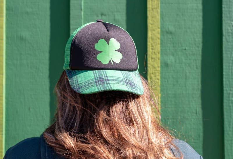Chapéu vestindo do trevo da jovem mulher contra a parede verde fotos de stock royalty free