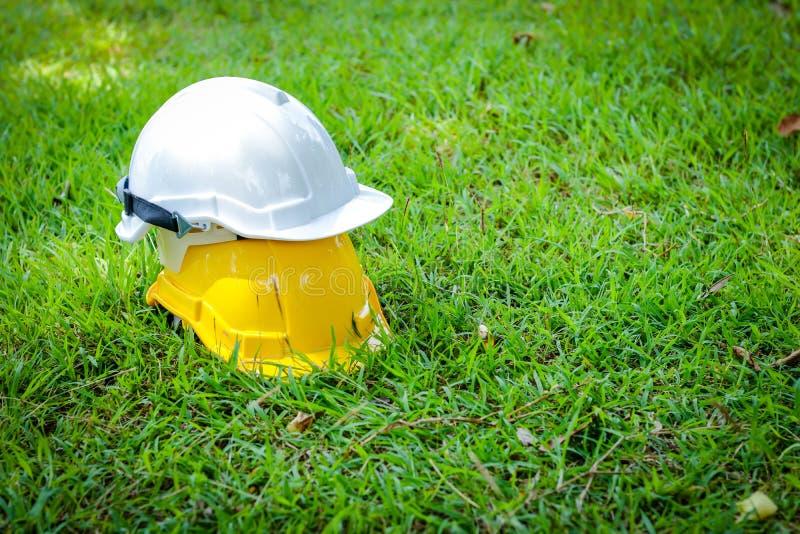 Chapéus de segurança amarelos e brancos colocados na grama imagem de stock royalty free