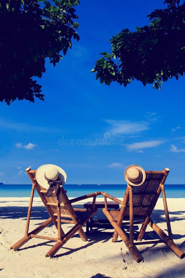 Chapéus em cadeiras da praia tropical imagem de stock