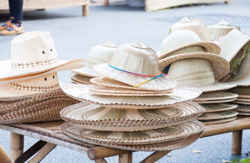 Chapéus feitos a mão tecidos do arranjo de bambu dos chapéus no mercado imagem de stock