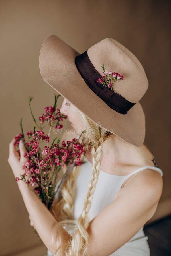Chap?u cinzento louro das flores do vestido da mulher foto de stock royalty free