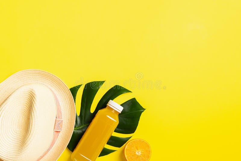 Chap?u do ver?o uma garrafa do suco de laranja em uma folha de um fundo amarelo brilhante da planta tropical O conceito do abrand fotografia de stock