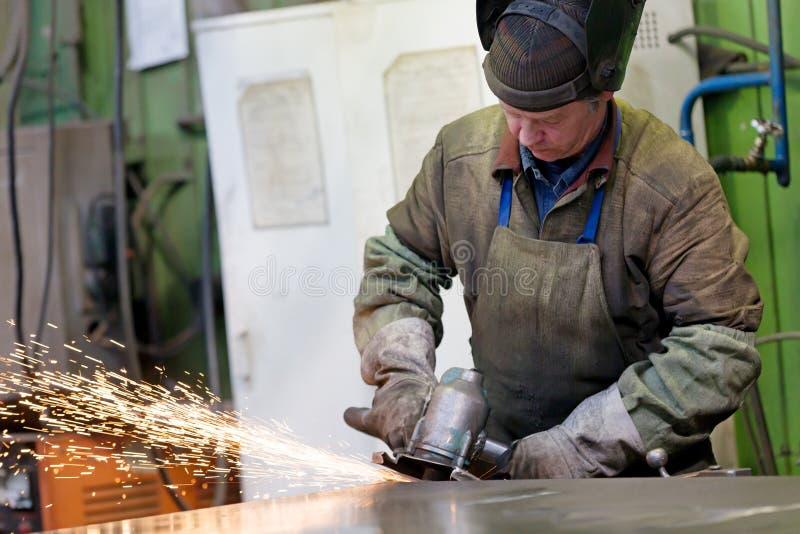 Chapa de aço de moedura do trabalhador do soldador da fábrica na oficina fotografia de stock royalty free