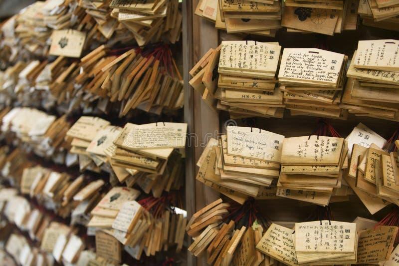 Chapas de madeira pequenas do santuário xintoísmo de Meiji-jingu do Tóquio de Japão com orações e desejos (Ema) fotografia de stock royalty free
