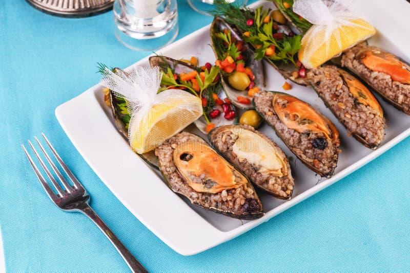 Chapas de mexilhões e ostras, cozidas com especiarias em bagas fotografia de stock