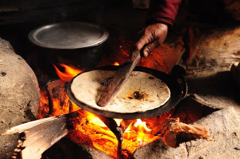 Chapati de traitement au four sur l'incendie en bois photos stock