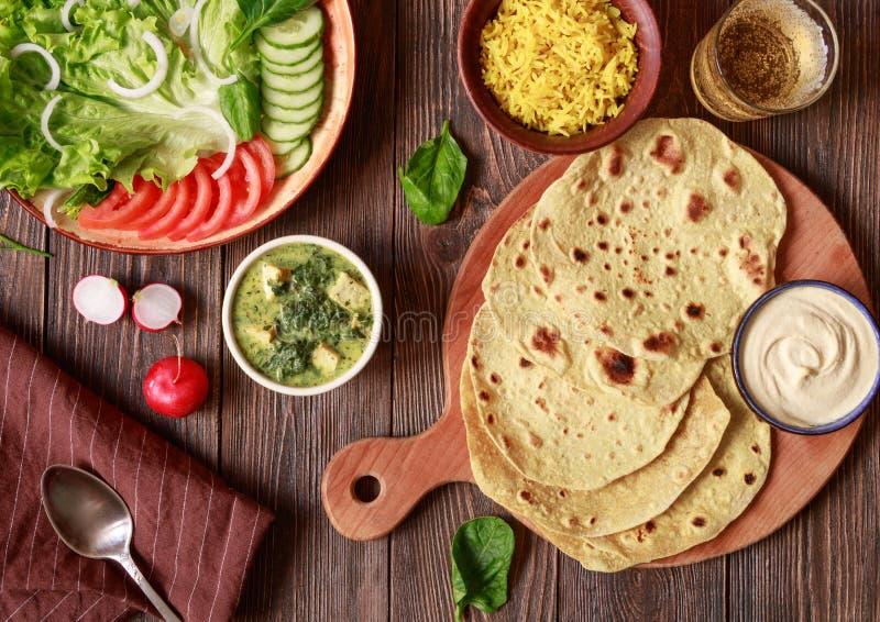 Chapati plat v?g?tarien indien de pain avec des l?gumes et houmous sur une table en bois photos stock