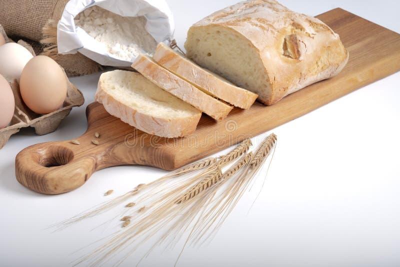 Chapatti coupé en tranches sur le conseil en bois entouré par des oreilles d'oeufs, de farine et de blé images libres de droits