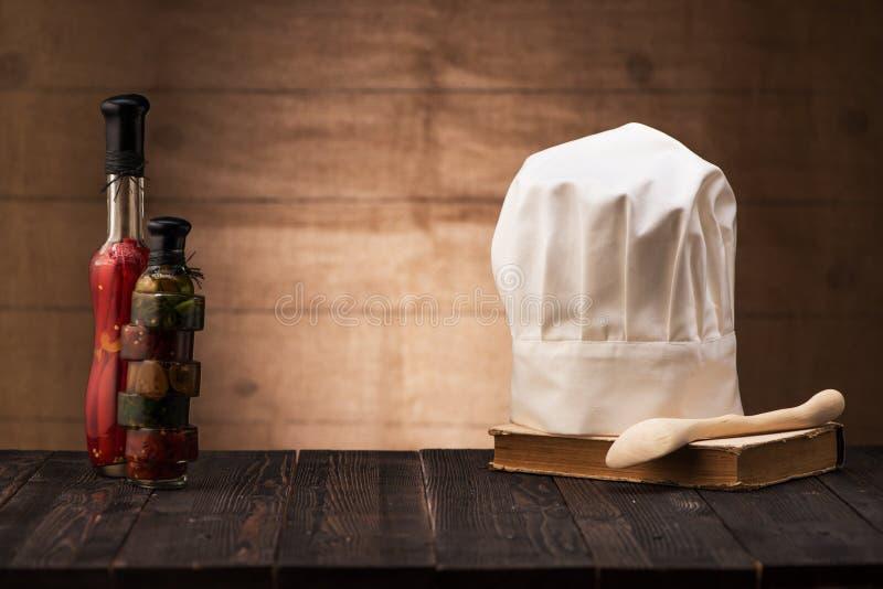 Chapeau blanc et vieux livre de cuisine sur la table de la cuisine photographie stock libre de droits