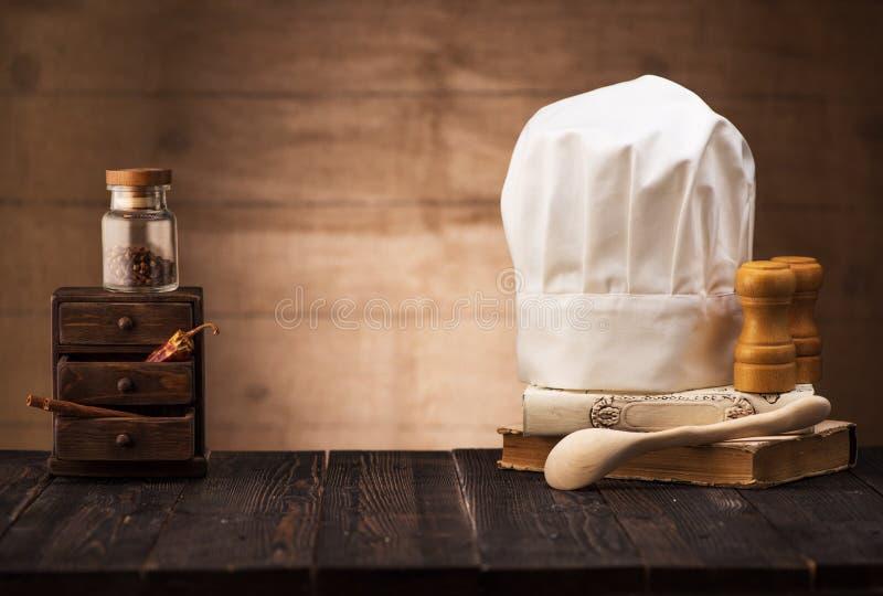 Chapeau blanc et vieux livre de cuisine sur la table de la cuisine image stock