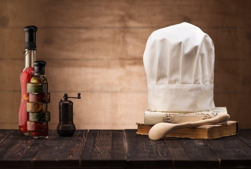 Chapeau blanc et vieux livre de cuisine sur la table de cuisine, cuillère en bois et épices image libre de droits