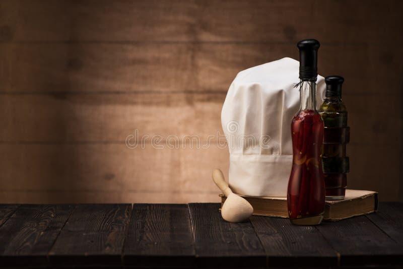 Chapeau blanc et vieux livre de cuisine sur la table de la cuisine photos stock