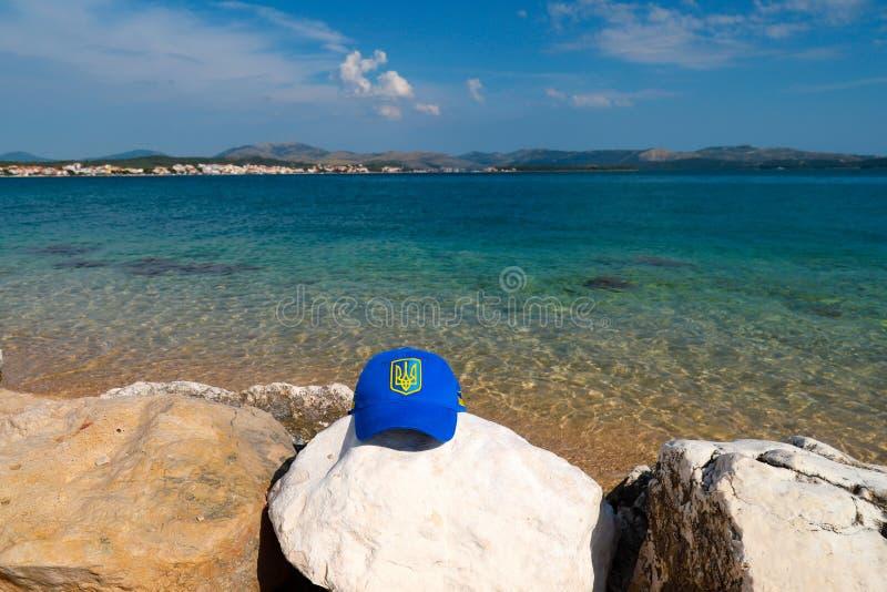 Chapeau bleu avec l'emblème de l'Ukraine sur le fond de la plage sur les rivages de la mer, rivière, océan ?t? ukrainien image libre de droits