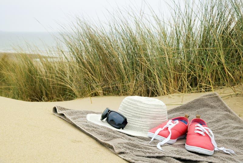 Chapeau, chaussures et verres de soleil sur la serviette de plage image stock