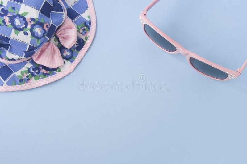Chapeau coloré et lunettes de soleil roses sur b en pastel bleu-clair photos stock