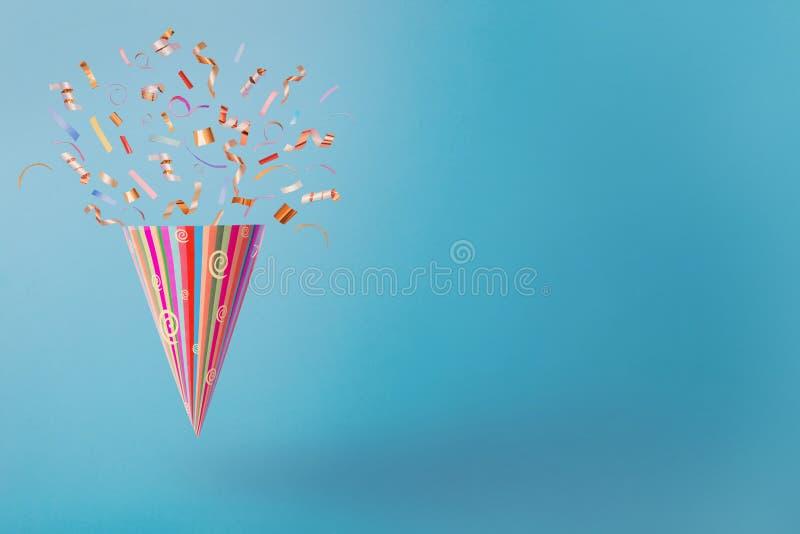Chapeau d'anniversaire avec des confettis sur le fond de papier bleu image stock