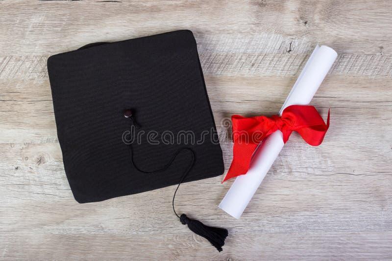 chapeau d'obtention du diplôme, chapeau avec le papier de degré sur le concept en bois d'obtention du diplôme de table photographie stock libre de droits