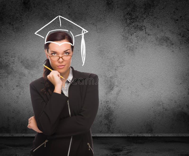Chapeau d'obtention du diplôme dessiné sur la tête de la jeune femme adulte avec le crayon devant le mur avec l'espace de copie images stock