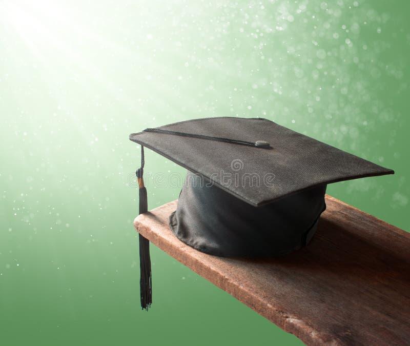chapeau d'obtention du diplôme, chapeau sur le bois avec le gradua de fond de vert d'abstrac photos stock