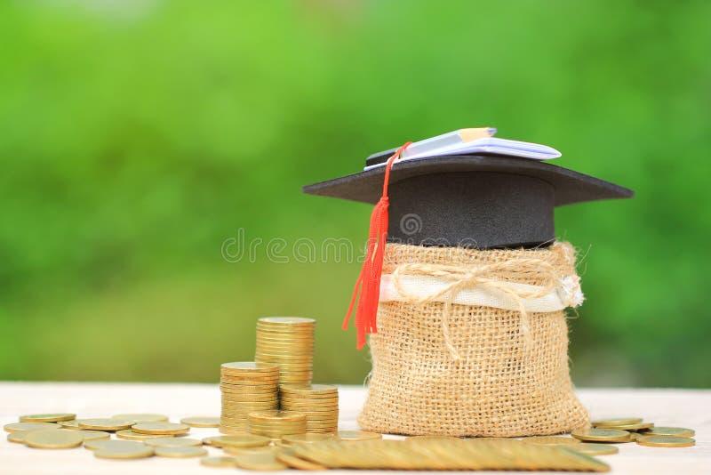 Chapeau d'obtention du diplôme sur le sac avec la pile d'argent de pièces d'or sur le natu image stock