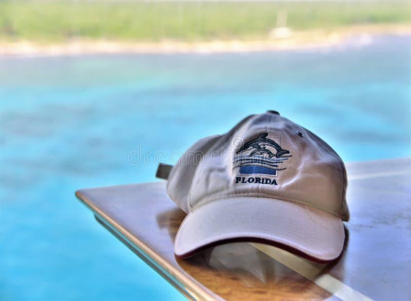Chapeau de base-ball blanc de la Floride avec de l'eau turquoise à l'arrière-plan photographie stock