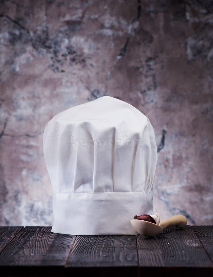 Chapeau de chef et cuillère en bois images libres de droits