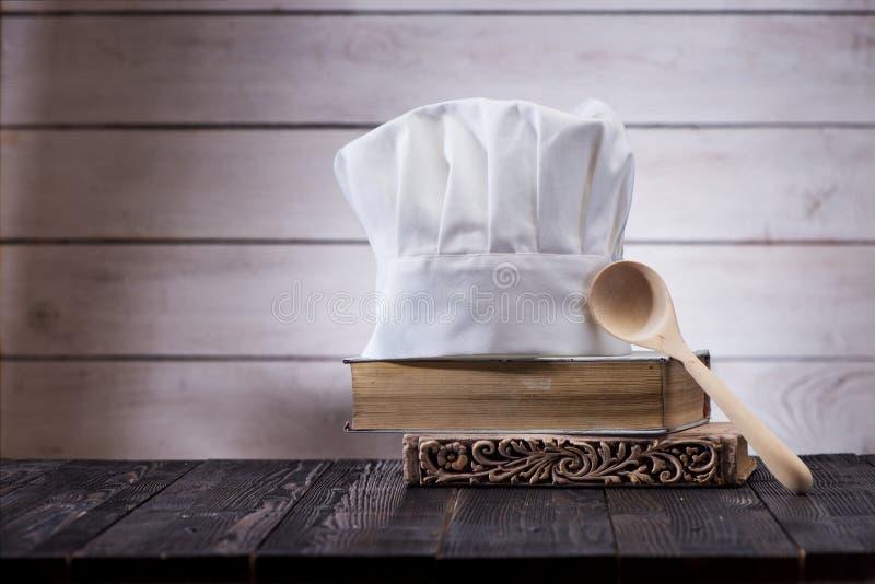 chapeau de chef, livres anciens et cuillère en bois sur la table de cuisine  photo stock