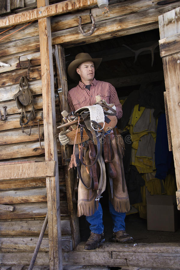 Chapeau de cowboy s'usant d'homme retenant une selle photographie stock