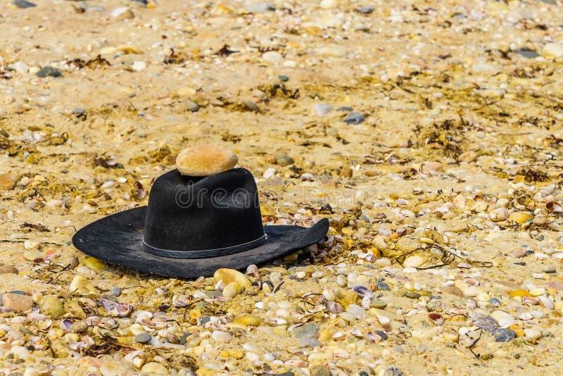 Chapeau de feutre noir sur des cailloux sur le Long Island de plage de l'Orient images stock