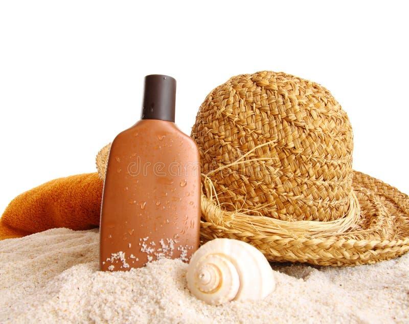 Chapeau de paille avec la serviette et lotion de bronzage sur le blanc photographie stock