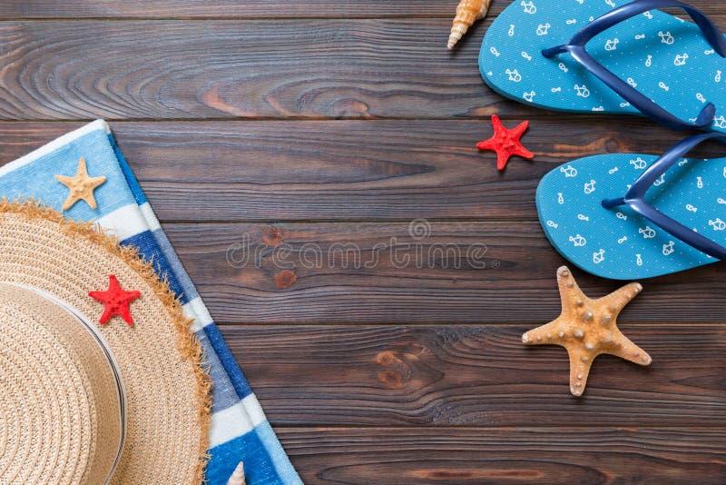 Chapeau de paille, bascules ?lectroniques bleues, serviette et ?toiles de mer sur un fond en bois fonc? concept de vacances d'?t? photographie stock