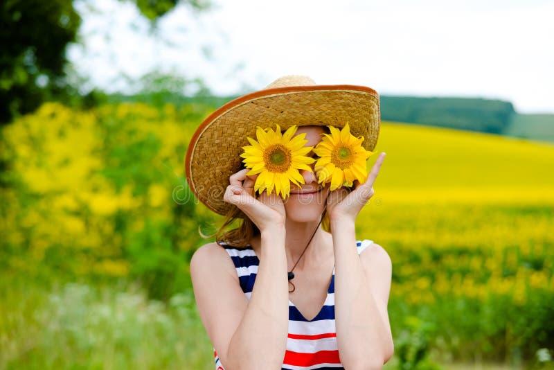 Chapeau de paille de port de jeune femme avec deux tournesols images stock