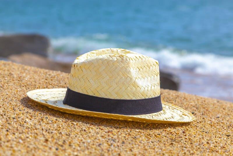 Chapeau de paille du Panama et parapluie de plage sur la plage sablonneuse près de la mer Vacances d'été et concept de vacances p image stock